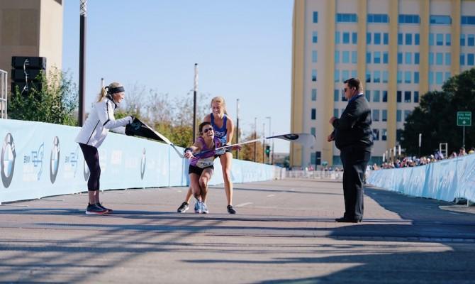 Crolla a 300 metri dal traguardo ma vince la maratona di Dallas grazie all'aiuto di un'avversaria